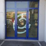 Vetrofania: adesivo sabbiato con inserto adesivo bianco con ripresa del logo del negozio. Vista da fuori.