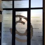 Vetrofania: adesivo sabbiato con inserto adesivo bianco con ripresa del logo del negozio. Vista da dentro.